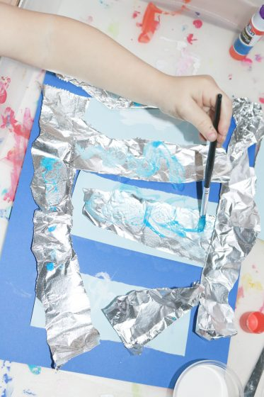 preschooler painting aluminum foil that's attached to cardstock