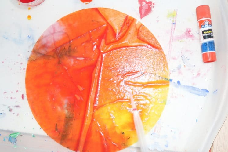 red, orange, and yellow paint on coffee filter to make sunset process art