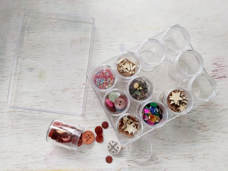 clear container filled with small translucent canisters for organizing embellishments