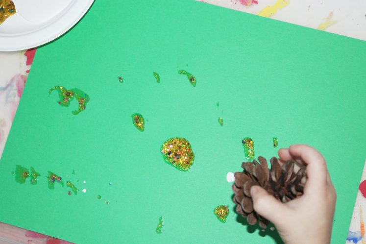 preschooler stamping pinecone covered in paint on cardstock