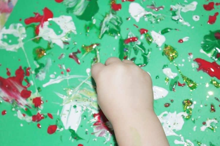 preschooler sprinkling gold glitter onto pinecone process art