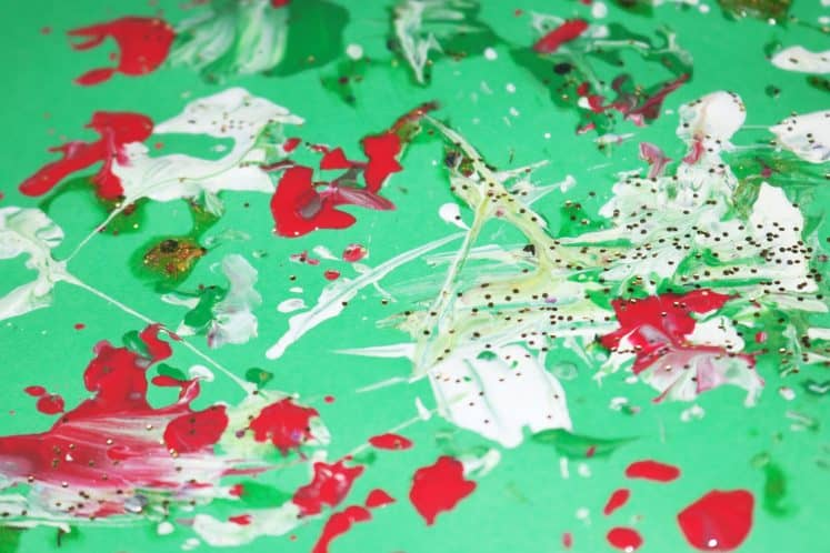 pinecone painting with red, white, yellow, and green paint