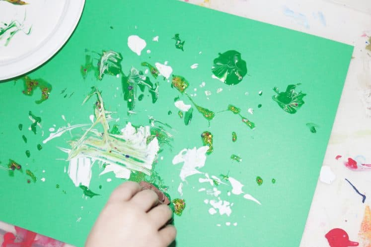 preschooler making pinecone process art using pinecone and paint