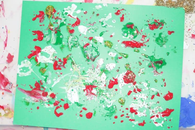 preschooler's finished pinecone painting for kids with red, white, gold, and green