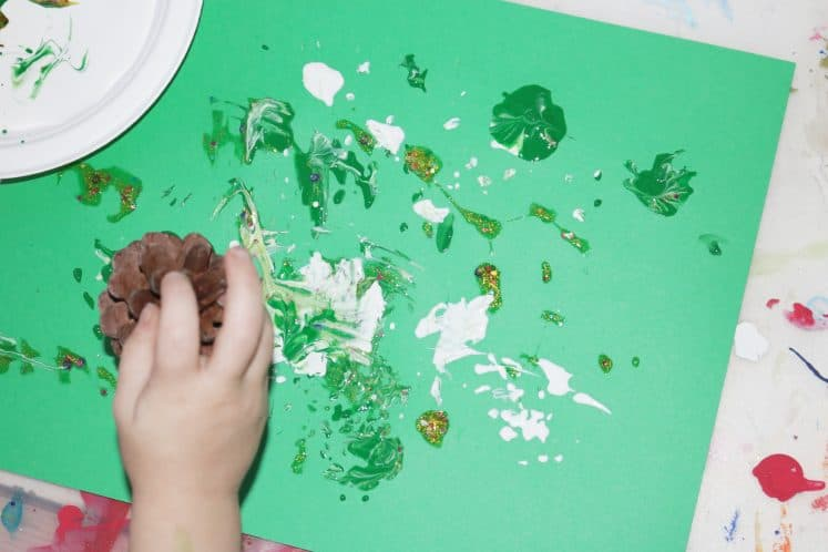 preschooler stamping on cardstock using pinecone and paint