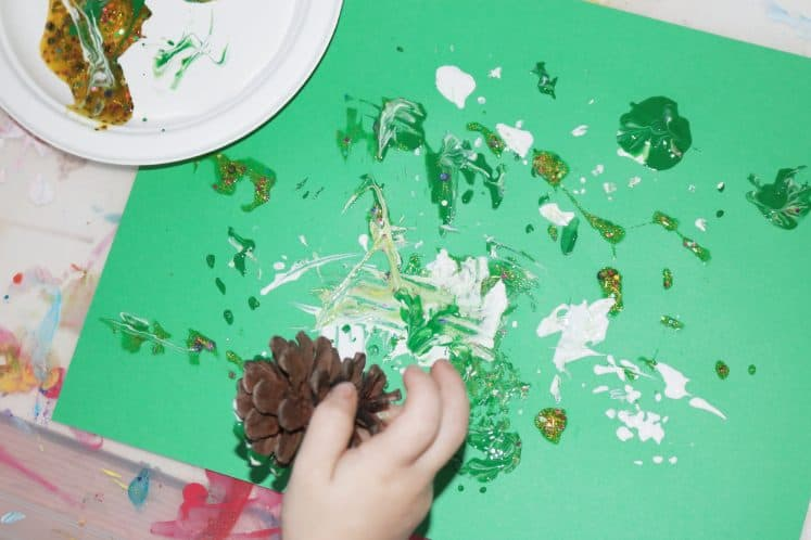 preschooler painting by dipping pinecone into paint and then stamping pinecone on cardstock
