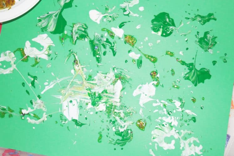 pinecone process art with white, gold, and green paint splatters