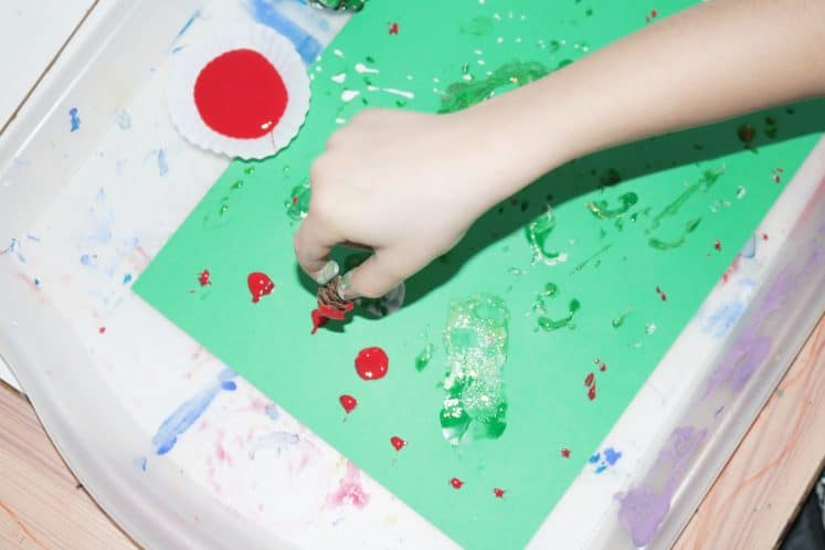 preschooler stamping pinecone with red paint onto cardstock