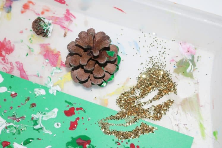 pinecone and gold glitter on tray with preschooler's pinecone process art