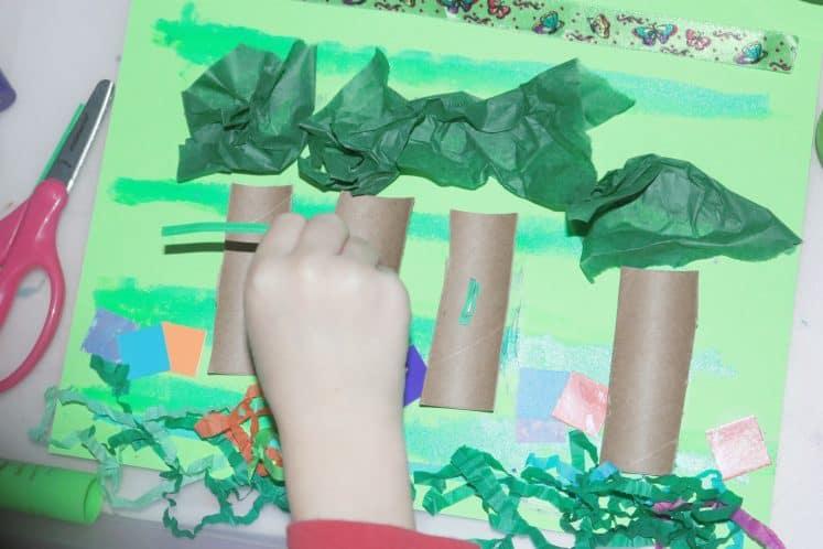 child making rainforest collage art