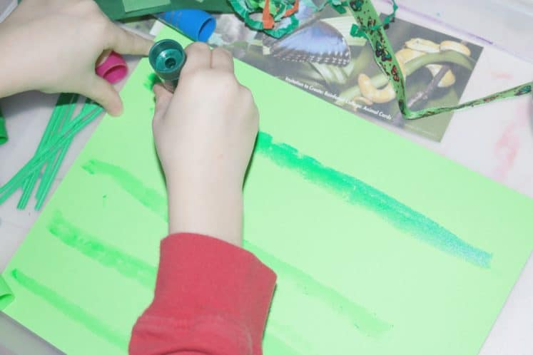 child drawing layers of rainforest using paint stick