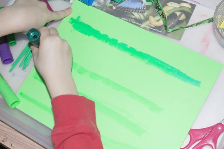 child using paint stick to create rainforest collage