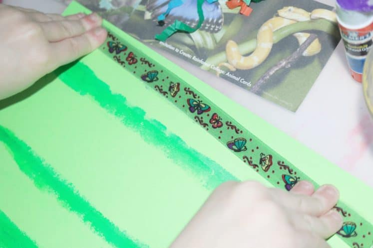 child adding a piece of butterfly ribbon to rainforest collage