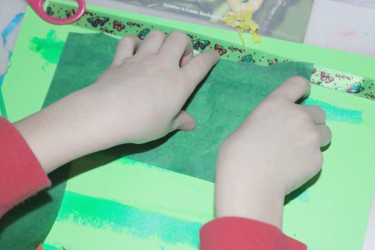 child using tissue paper to create rainforest collage
