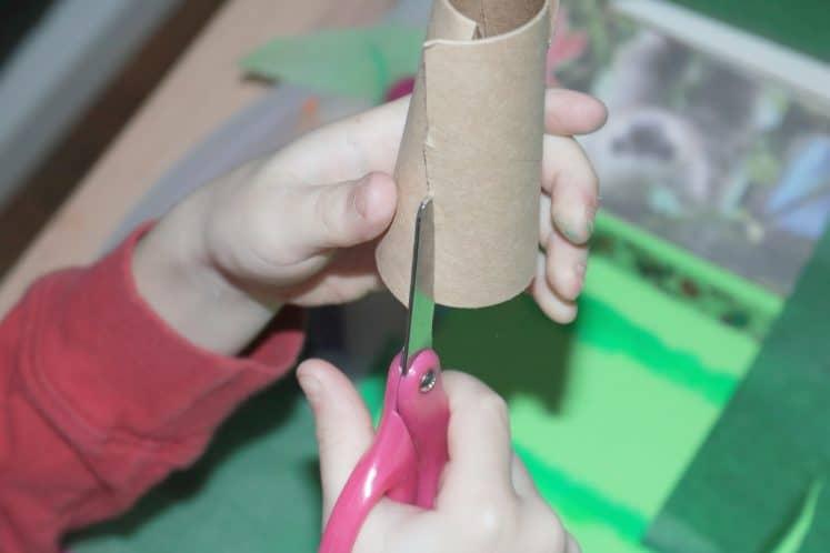 child cutting cardboard roll to make tree trunks
