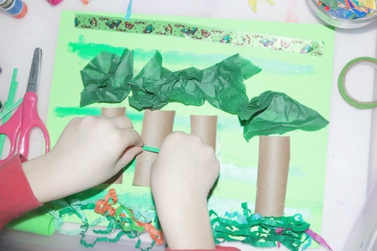 child adding green twist tie to rainforest collage