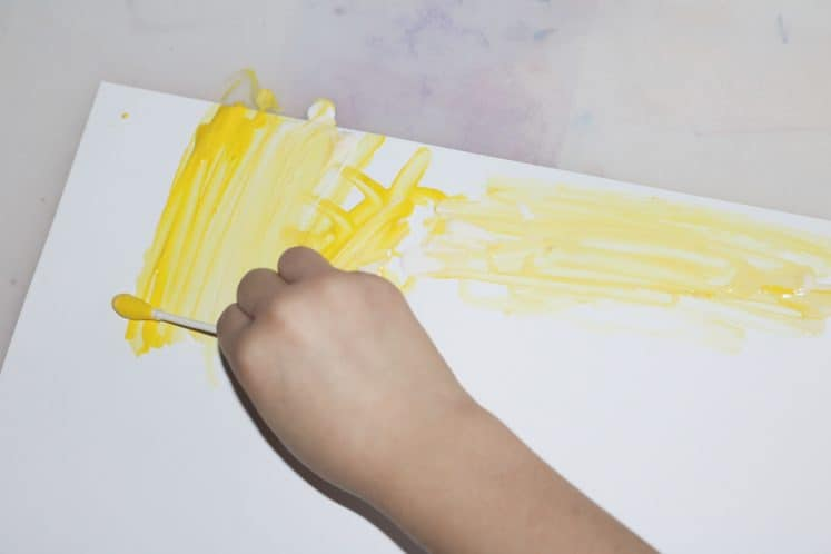 child using cotton swab to add yellow paint to tree painting