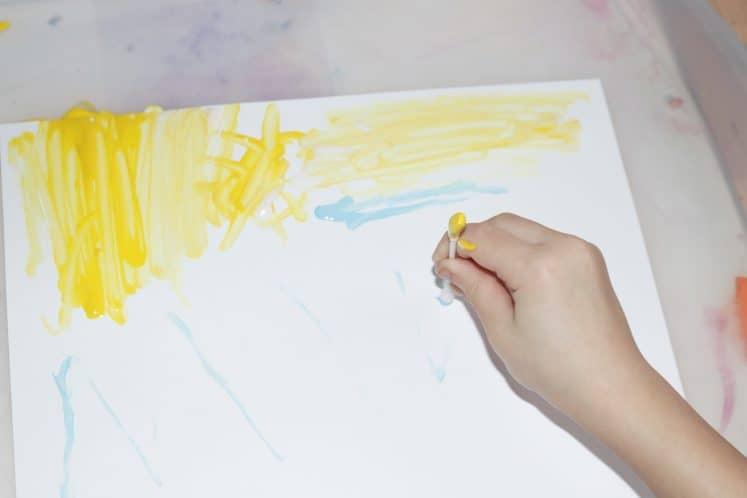 child adding yellow paint to tree painting using cotton swab