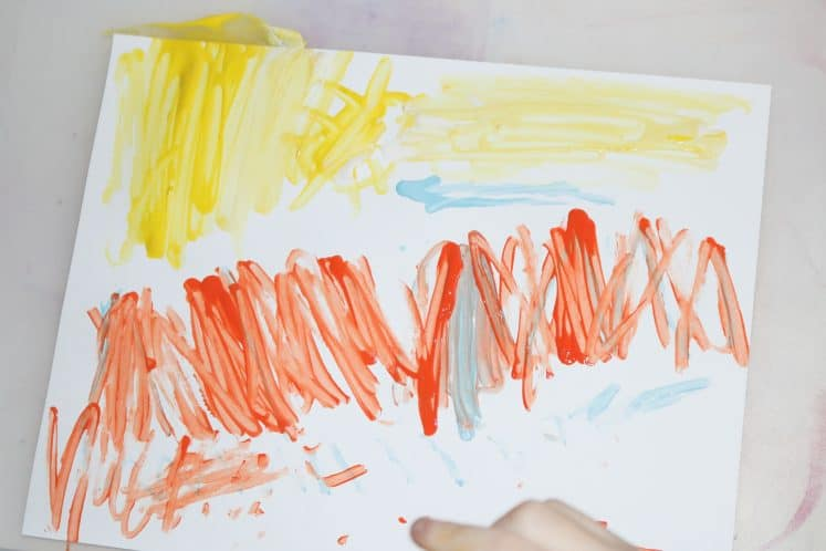 child painting tree line with cotton swab