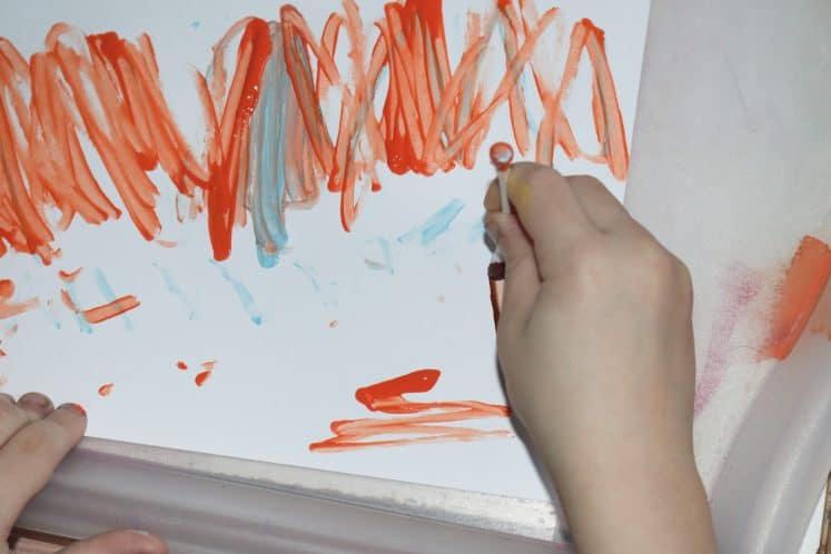 child painting trees using cotton swab to create tree painting process art
