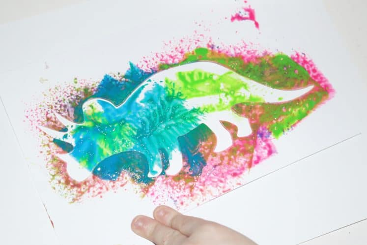 child making dinosaur process art using paint and stencil