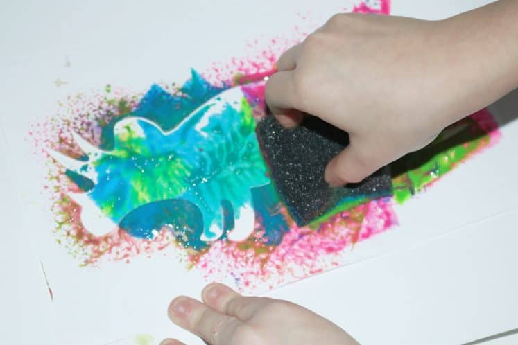 child using a sponge and dinosaur stencil to paint
