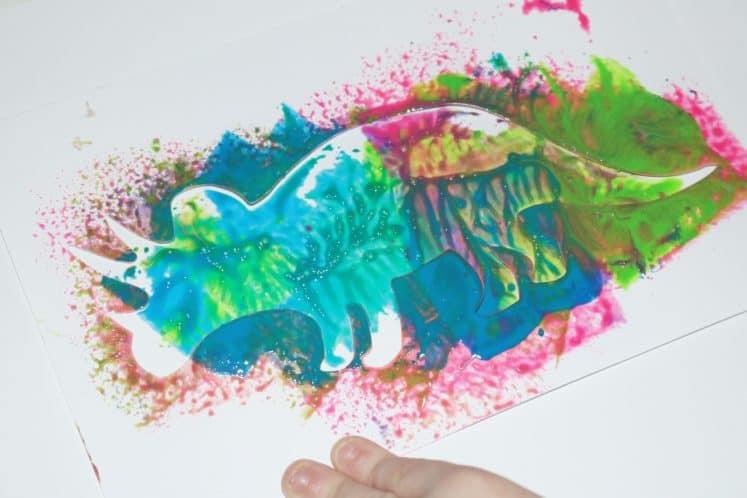 child's dinosaur process art using stencil
