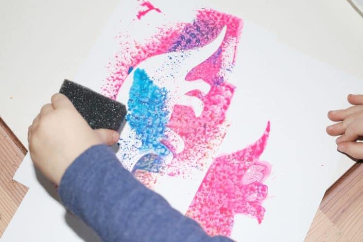preschooler sponge painting using dinosaur stencil