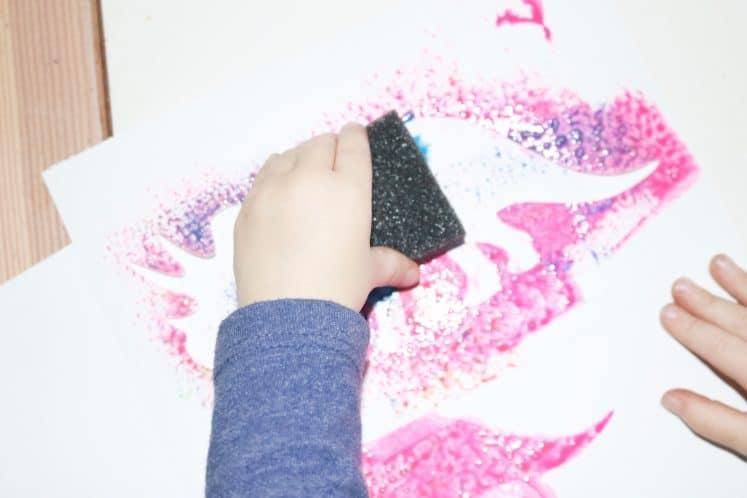 preschooler sponge painting with stencil