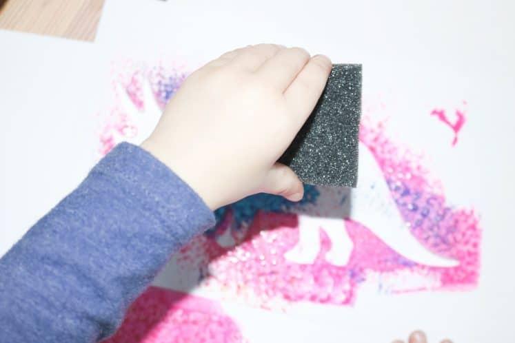 preschooler sponge painting using paint and dinosaur stencil