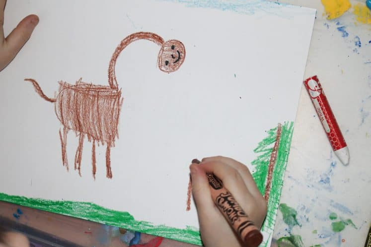child coloring dinosaur with crayon