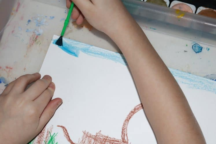 child painting sky with watercolor