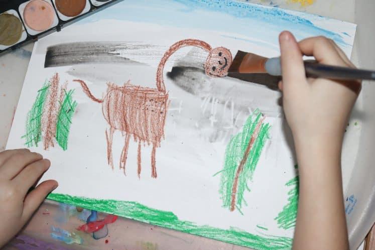 child adding gray watercolor to dinosaur process art