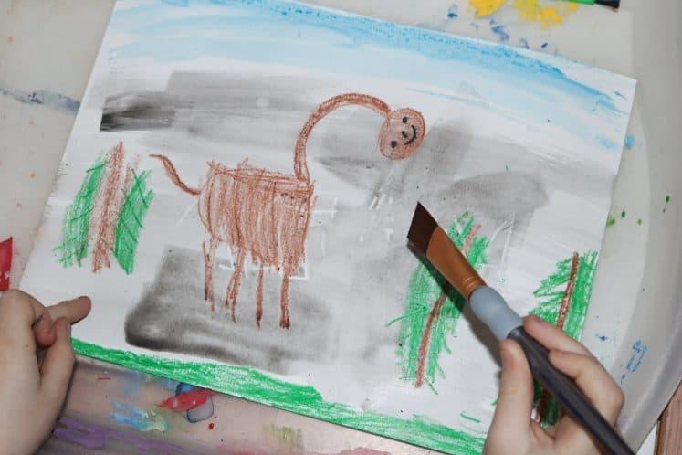 child painting background of dinosaur resist process art