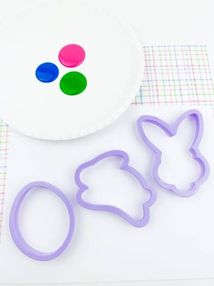 Easter cookie cutter next to paint on paper plate