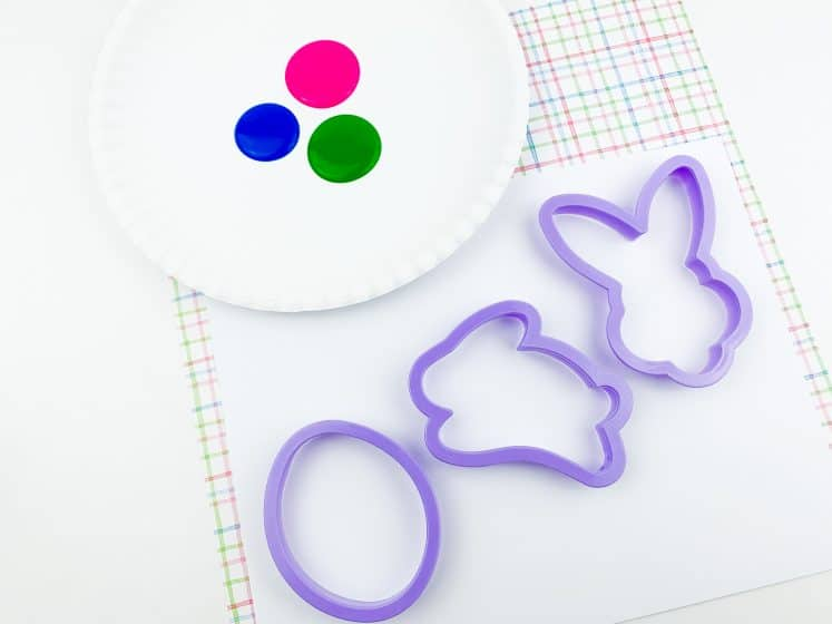 Easter cookie cutters next to paint on paper plate