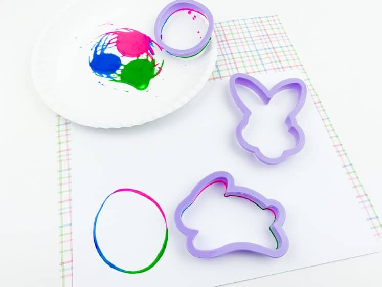 Easter process art using Easter cookie cutters and paint on white cardstock