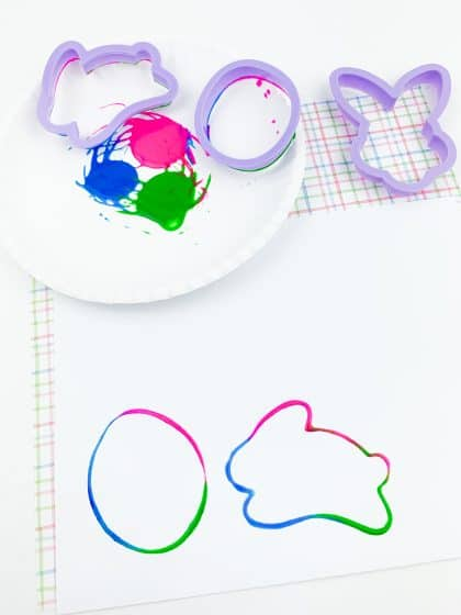 Easter egg and bunny stamped on white cardstock using cookie cutters and paint
