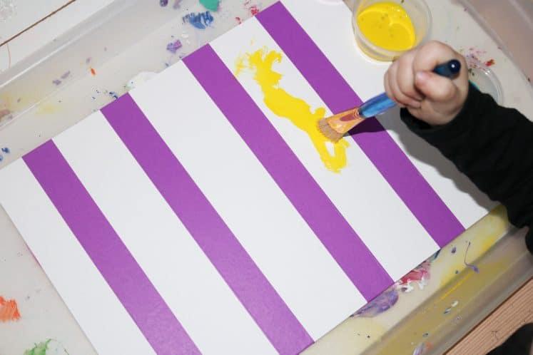 preschooler painting on cardstock