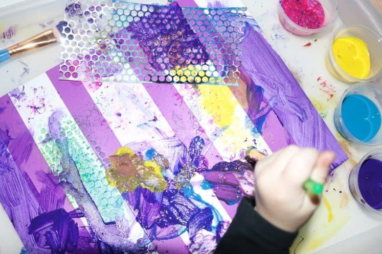 preschooler painting on cardstock using tape resist technique