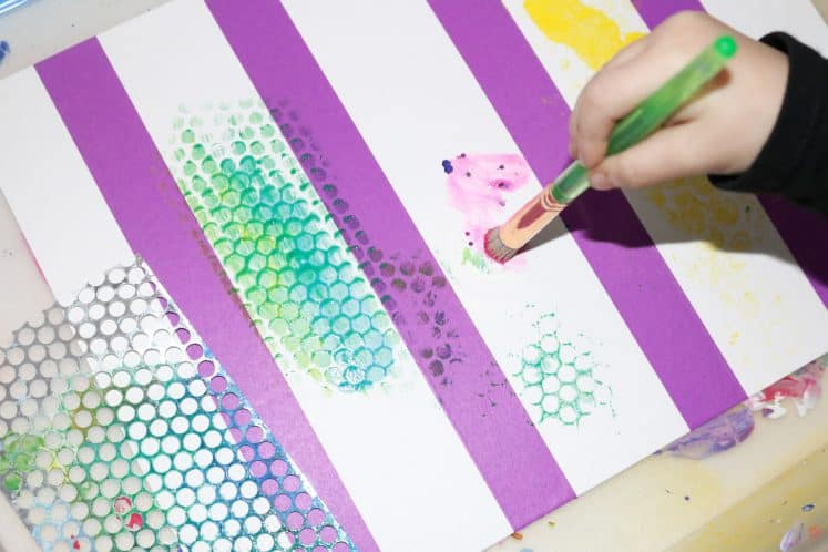 preschooler painting on cardstock with glitter paint