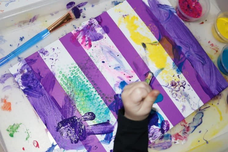 preschooler painting using brushes on cardstock