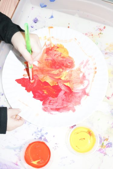 preschooler painting on paper plate to make sun craft