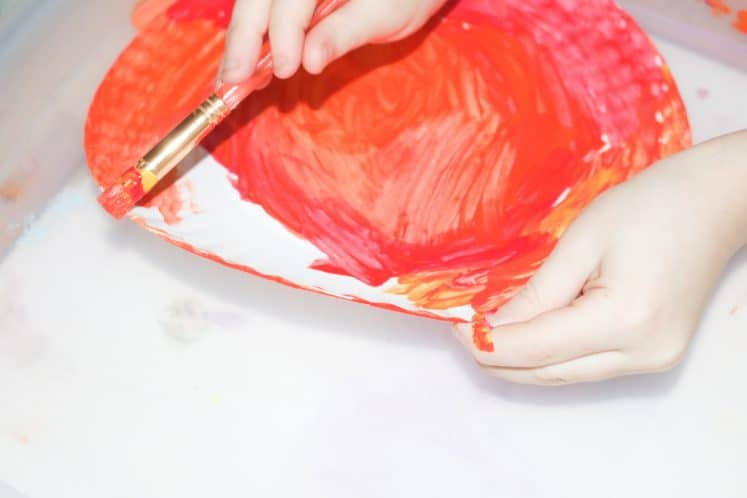 child making paper plate sun with paint