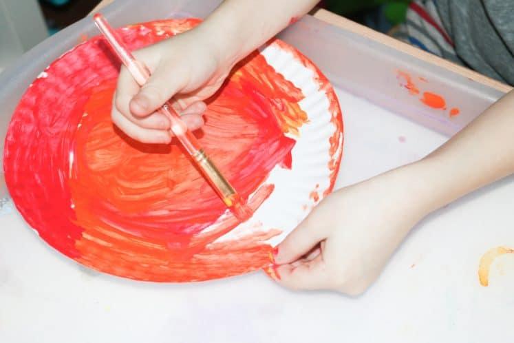 child making paper plate sun craft using paint