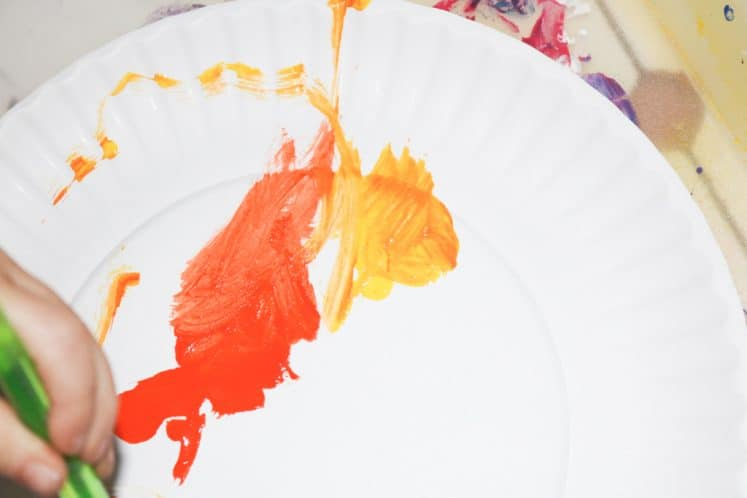 child painting paper plate using orange and yellow paint