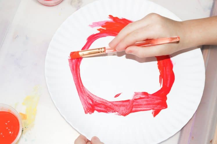 child making sun colors process art with paint and paper plate