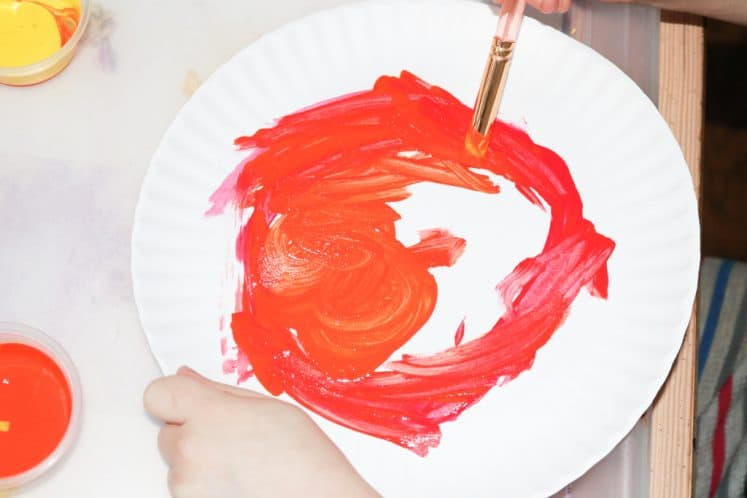 child painting sun on paper plate using red and orange paint