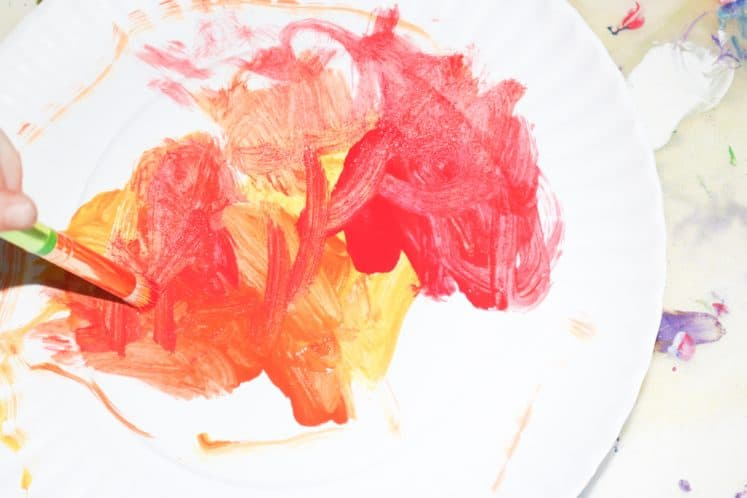 child painting paper plate to make sun craft