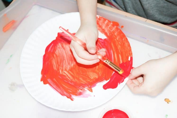 child painting paper plate sun using red paint